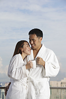 Young couple in robes smiling at each other - Yukmin