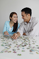 Young couple working on puzzle together - Yukmin