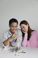 Young couple saving money in a jar - Yukmin
