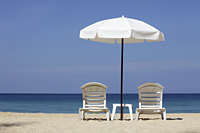 White umbrella and chairs on beach - Yukmin