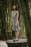 Young woman standing on a rock in bamboo forest - Yukmin
