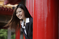 Young woman looking out from red pillars smiling - Yukmin