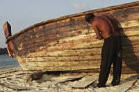 Asian man fixing boat on the beach - Yukmin
