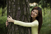 Chinese woman hugging a tree and smiling - Yukmin