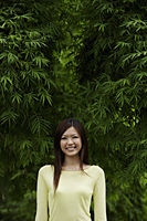 Young woman smiling in front of bamboo trees - Yukmin