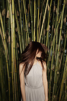 Young woman shaking her hair in front of bamboo - Yukmin