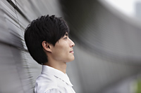 Profile shot of man leaning against wall - Yukmin