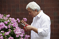 Older man smelling flowers in garden - Yukmin