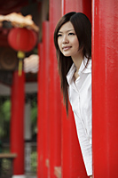 Young woman looking out from behind red pillars - Yukmin