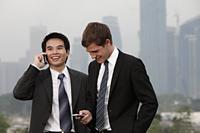 Chinese man talking on phone while Caucasian man texts. - Yukmin