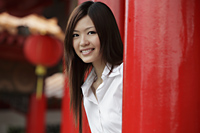 Young woman smiling at camera in front of Chinese temple - Yukmin