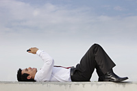 man in suit laying on ground looking at phone, smiling - Yukmin