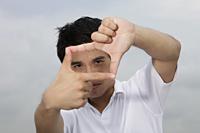 Asian man looking through finger frame - Yukmin