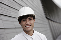 man wearing construction hat smiling in front of building - Yukmin