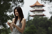 Young woman holding white flower in front of pagoda - Yukmin