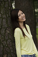 Young woman leaning against tree and smiling - Yukmin