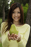 Young woman holding a yellow pear - Yukmin