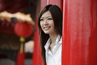 Chinese woman looking out from behind red pillars - Yukmin