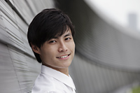 Head shot of man smiling in front of wall - Yukmin