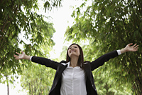 Young woman wearing a suit and raising her arms up outside - Yukmin