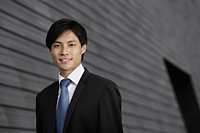Chinese man wearing a suit smiling in front of building - Yukmin