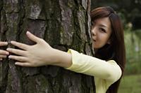 Young woman hugging tree - Yukmin