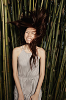 Young woman flipping her hair in front of bamboo - Yukmin