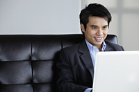 Chinese man using laptop and smiling - Yukmin