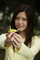 Young woman holding yellow crane - Yukmin