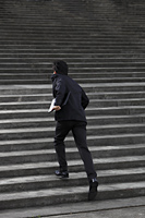 Man running up stairs wearing a suit - Yukmin