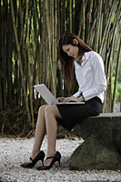 Chinese woman working on lap top in bamboo garden - Yukmin