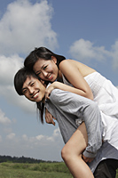 young man carrying a woman on his back outside - Yukmin