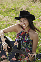 Smiling woman playing guitar in grassy field. - Yukmin