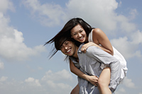 young man carrying a woman on his back laughing, blue sky with clouds as background - Yukmin
