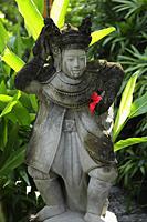 stone Hindu statue with red flower - Alex Mares-Manton