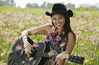 smiling woman playing guitar in grassy field - Yukmin