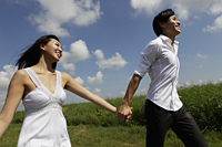 young couple holding hands and smiling outside - Yukmin