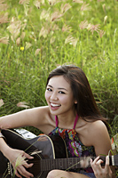 smiling woman playing guitar on grass - Yukmin