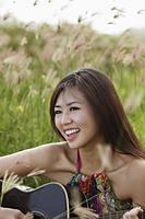 smiling woman playing guitar outside - Yukmin