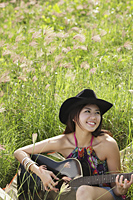 smiling woman playing guitar outside on the grass - Yukmin