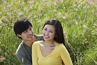 Young couple sitting on grass smiling together - Yukmin