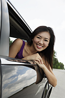 young woman leaning out of car window smiling - Yukmin