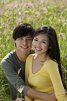 Young couple holding each other in a field - Yukmin
