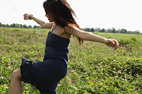 young woman dancing in grassy field - Yukmin