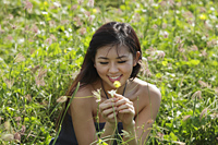 young woman looking at flower in grassy field - Yukmin