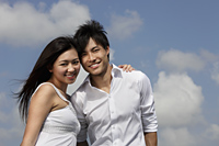 young couple smiling together with blue sky and clouds as background - Yukmin