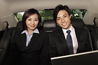 man and woman wearing business suits in back seat of car - Yukmin