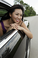 young woman looking out car window smiling - Yukmin