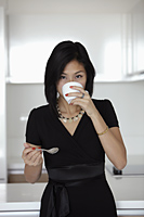 young woman drinking out of coffee mug - Yukmin