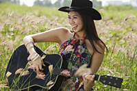 Happy woman playing guitar in grassy field - Yukmin